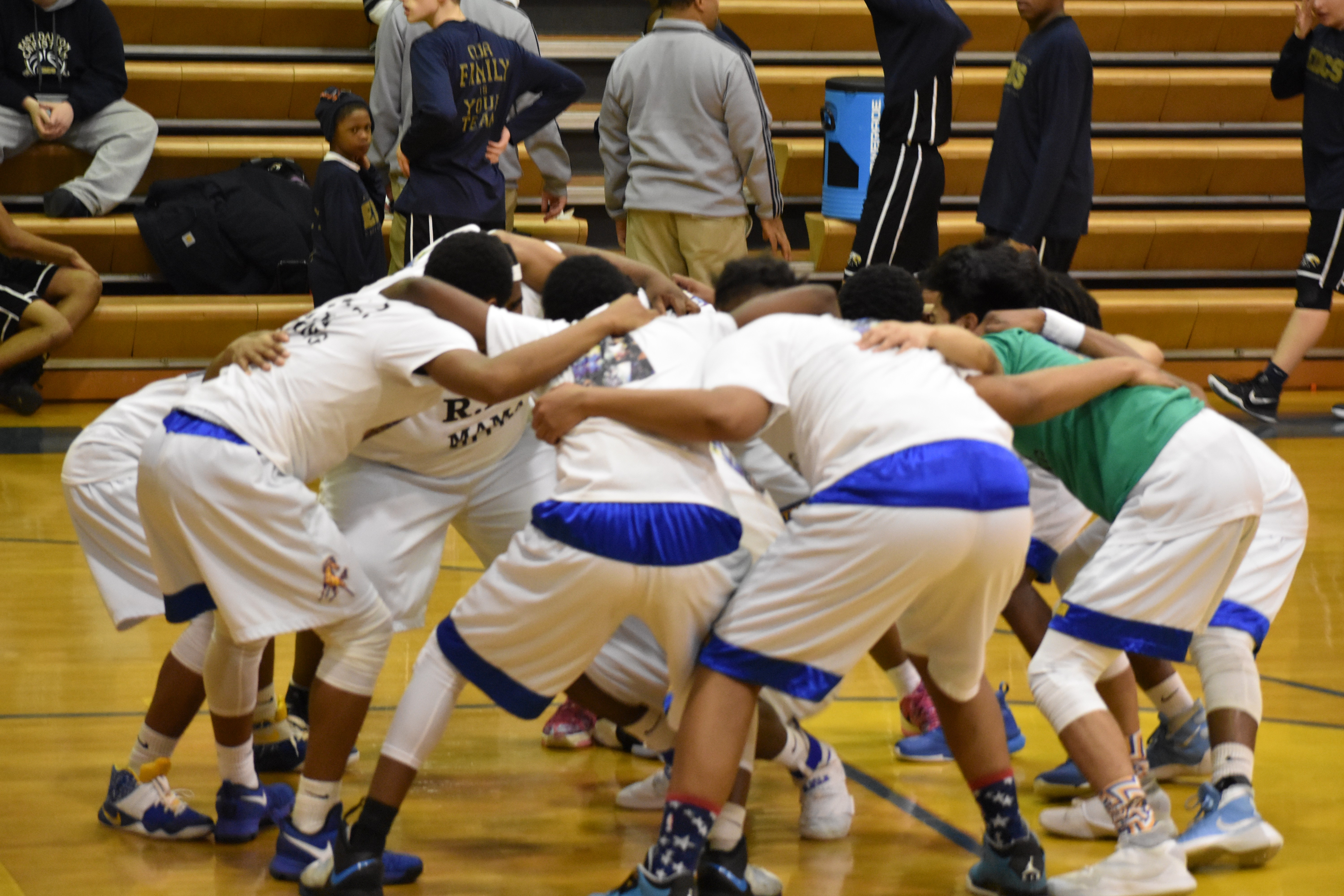 Bronco varsity basketball team huddled before a game in 2017.